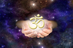 Om - The Sound of the Universe. Cupped hands emerging from deep space background with golden 'om' floating above hands Stock Photos