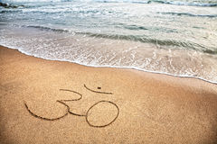 Om symbol on the beach. Om symbol on the sand at the beach near the ocean Stock Image