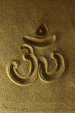 Om symbol hand drawn in the sand. Golden sand Stock Photos
