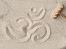 Om symbol in sand. Om symbol written in sand, view from above, have a break or meditation concept Stock Image