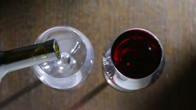 Om twee glazen rode wijn te gieten Hoogste mening Mannelijke en vrouwelijke handen stock footage