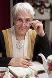 Oma in den Gläsern schreibt einen Brief Stockfoto