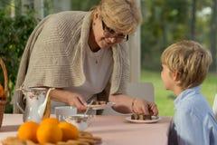 Oma die omhoog eigengemaakte cake dishing royalty-vrije stock foto's