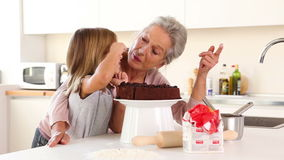 Oma die suikerglazuur op kleindochtersneus zetten stock video