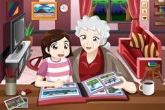 Oma en kleindochter die beeldalbum bekijken Stock Afbeeldingen
