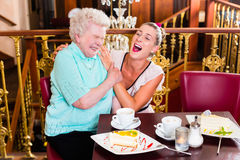 Oma en kleindochter die in koffie lachen Stock Foto