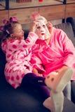 Oma en kleindochter die roze badjassen dragen die bladmasker nemen stock fotografie