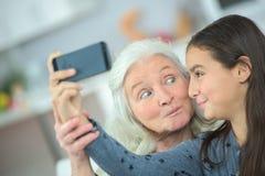 Oma en meisje die foto zelf nemen Stock Foto