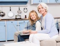 Oma en meisje die laptop met behulp van Stock Fotografie