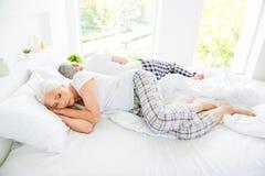 Oma, het paarslaap van het opa grijze haar op groot bed rijtjes stock foto