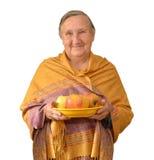 Oma im gelben tippet hält eine Platte mit Äpfeln Stockbilder