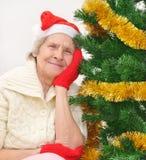 Oma im roten Weihnachtsmann-Hut und in den roten Handschuhen lizenzfreies stockfoto