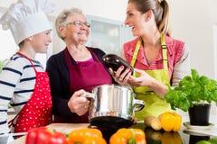 Oma, Mama und Sohn, die beim Kochen in der Küche sprechen Lizenzfreies Stockfoto
