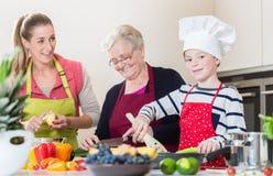 Oma, Mama und Sohn, die beim Kochen in der Küche sprechen Lizenzfreies Stockbild
