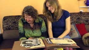 Oma met kleindochter die lang foto van oud album bekijken stock video