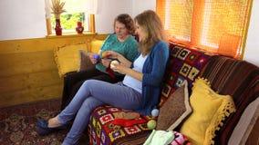 Oma mit Enkelin beschließen Threadfarbe, um Babysocken zu stricken stock video footage