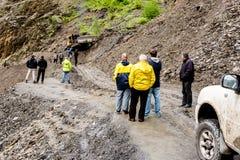 Omalo, Geórgia - 11 de junho de 2016: Trabalhadores com trator para remover o corrimento na estrada da montanha, Tusheti imagem de stock