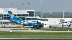Oman Air spiana facendo il taxi sulla pista nell'aeroporto di Monaco di Baviera, MUC stock footage