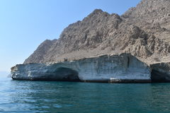 Oman. A beautiful view of the creamish brown mountains and the deep blue  in a place called Musandam near Oman Stock Photos
