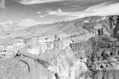 in Oman die alte Gebirgsschlucht und -schlucht der tiefe bewölkte Himmel Stockfotografie