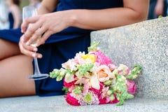 Oman in einem dunkelblauen Kleid, das auf Steintreppe mit einem Glas des Champagners und des hellen rosa und weißen Hochzeitsblum lizenzfreie stockbilder