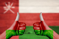 Oman flag painted on female hands thumbs up Royalty Free Stock Image