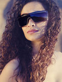 Oman with gorgeous curly hair wearing sunglasses Stock Photo