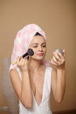 Oman in towel on the head applying makeup Royalty Free Stock Photo