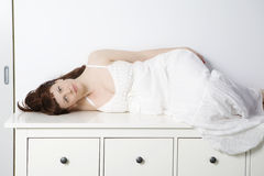 Oman wearing white dress  lying on chest of drawer Stock Images
