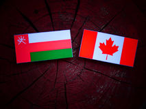 Omani flag with Canadian flag on a tree stump isolated Stock Image