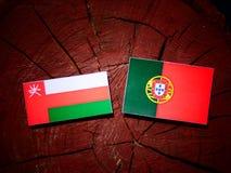 Omani flag with Portuguese flag on a tree stump isolated. Omani flag with Portuguese flag on a tree stump stock illustration