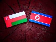 Omani flaga z koreańczyk z korei północnej flaga na drzewnym fiszorku Fotografia Stock
