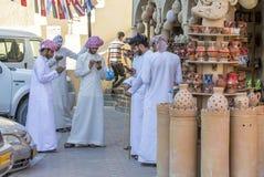 Omani mężczyzna przy rynkiem, wszystko w ich telefonów komórkowych texting Fotografia Royalty Free