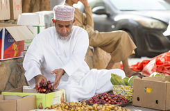 Omani man selling dates. Nizwa, Oman, June 24th, 2017: omani man in traditional clothing selling new swason dates at a street market Royalty Free Stock Photography