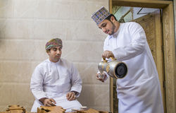 Omani man serving traditional coffee called qahwa to another oma Royalty Free Stock Image