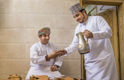 Omani man serving traditional coffee called qahwa to another oma Stock Image