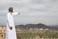 Arab man in traditional omani outfit pointing to the distance. Omani man in traditional clothing pointing to the distance in the countryside Stock Photography
