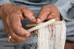 An Omani man weaving a fishing net. Stock Images