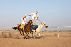Omani men showing off their riding skills. Stock Photography