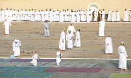 Omani men in traditional clothing socialising after a morning pr. Nizwa, Oman - June 26th 2017: omani men socialising after a Eid Al Fitr prayer in an outdoor Stock Photos