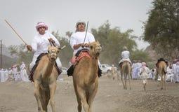 Omani mensen die kamelen berijden op een stoffige plattelandsweg Stock Afbeelding