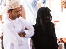 Omani para w tradycyjnym odziewa z kobietą jest ubranym przesłonę i maskę przy Piątku rynkiem w Nizwa zdjęcie stock