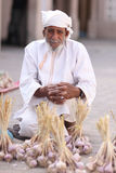 Omani salesman with traditional clothing. Man with traditional clothing in Oman, at a  market selling garlic Stock Photography