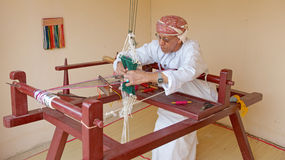 Omani Weaver. An Omani weaver, wearing a traditional muzzar (headcloth), at work in Muscat, in the Sultanate of Oman Stock Images