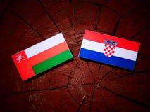 Omansk flagga med den kroatiska flaggan på en isolerad trädstubbe Royaltyfria Bilder