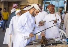 Omansk man som köper ett svärd Arkivfoton