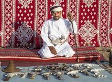 Omansk man som säljer traditionella khanjar dolkar Arkivbilder