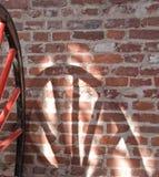Ombra dei raggi e della rotella sulla parete Immagine Stock