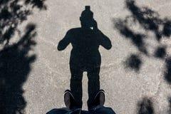 Ombra del fotografo sulla pavimentazione Fotografia Stock