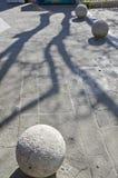 Ombra dell'albero sulla pavimentazione della via con la sfera rotonda della pietra decorativa Fotografia Stock